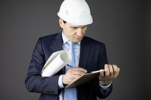 L'ingegnere capo nel casco di sicurezza prende appunti sugli appunti con il rotolo di progetto
