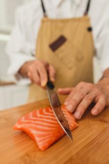 Un capo che affetta il salmone crudo pesce da vicino le mani con il coltello shot sushi banner sfondo
