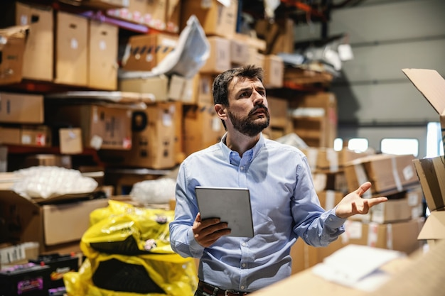 Capo in piedi in un deposito pieno di scatole pronte per la spedizione e tenendo la compressa. azienda di esportazione.