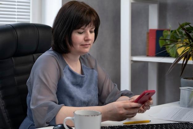 Capo sul posto di lavoro con il telefono in mano. la donna di affari decide le edizioni di affari. il segretario sta facendo scorrere il telefono durante il pranzo.