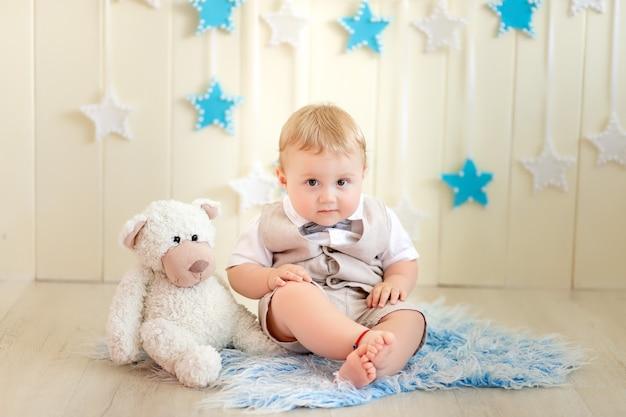 Bambino di 1 anno un ragazzo vestito con un vestito siede con un orso in un wigwam in uno studio fotografico, compleanno di un bambino 1 anno