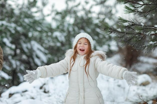 Bambino 5-6 anni in inverno nella foresta innevata sullo sfondo di alberi di natale