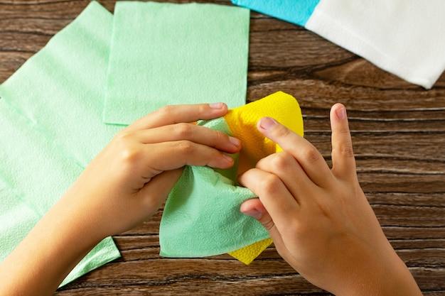Il bambino aggiunge un fiore dai tovaglioli progetto tavola festiva per bambini