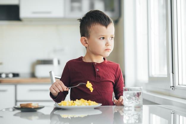 Un bambino nel pomeriggio in una cucina a luce bianca con un maglione bordeaux mangia una frittata
