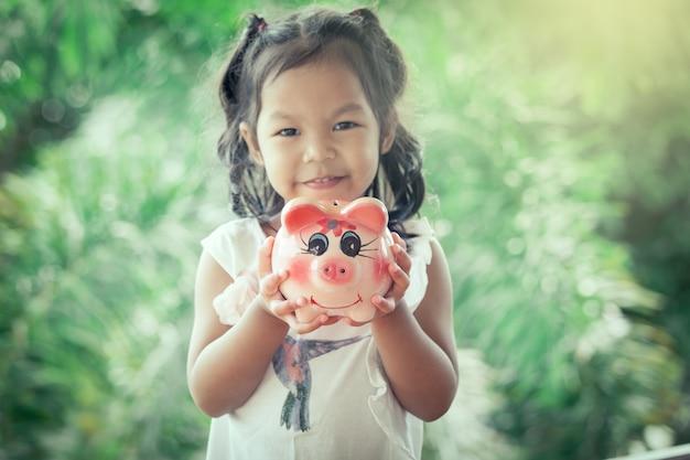 Bambina asiatica bambina in possesso di piggy bank in sfondo verde natura