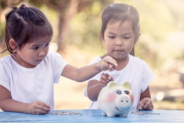 Bambina asiatica del bambino che mette moneta nel porcellino salvadanaio nel tono d'annata di colore