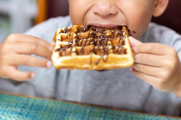 Cialda da bambino con sciroppo di cioccolato in cima