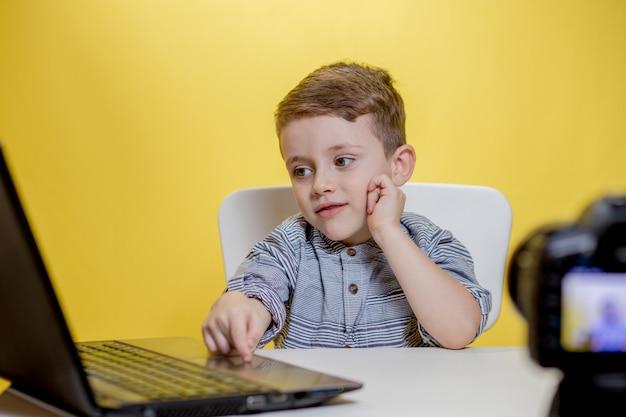 Il blogger bambino registra il suo vlog a casa. ragazzo che registra il suo video blog. il piccolo vlogger effettua lo streaming online utilizzando la fotocamera.