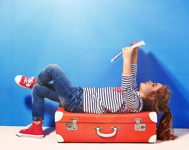 Bambina bionda con valigia vintage rosa e mappa della città pronta per le vacanze estive. concetto di viaggio e avventura.