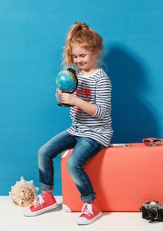 La ragazza bionda del bambino con la valigia vintage rosa studia il globo. concetto di viaggio e avventura.