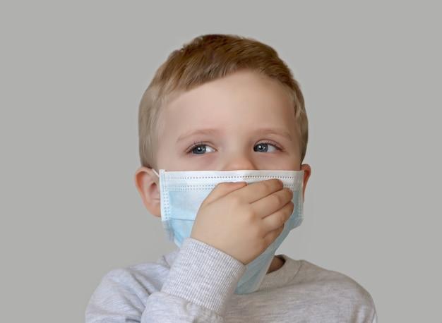 Il bambino in maschera medica blu chiude la bocca con la mano per tossire. fotografia ravvicinata. protezione della salute da vari virus e malattie. concetto di quarantena e prevenzione delle malattie.