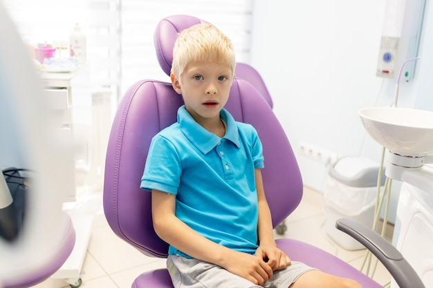 Un bambino un ragazzo di cinque anni è seduto su una sedia lilla in uno studio dentistico
