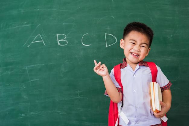 Ragazzo del bambino dall'asilo in uniforme studentesca con borsa di scuola e libro sulla testa