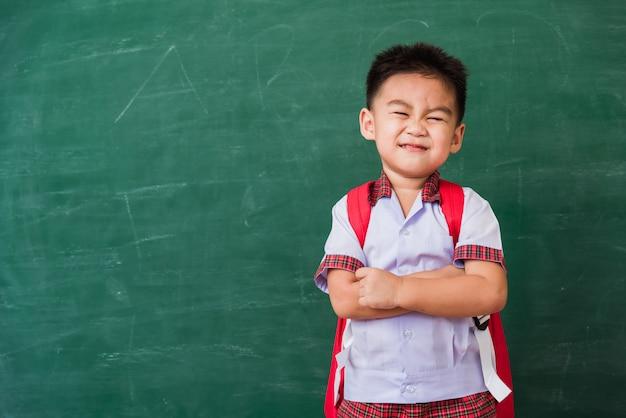 Ragazzo del bambino dall'asilo in uniforme dello studente con il supporto della borsa di scuola che sorride sulla lavagna della scuola