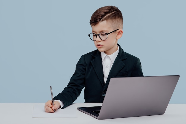 Bambino con gli occhiali e vestito che legge i dati dal laptop e prende appunti mentre è seduto al tavolo e...