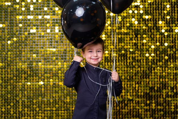 Bambino che tiene palloncini neri su sfondo con paillettes di paillettes dorate lucide