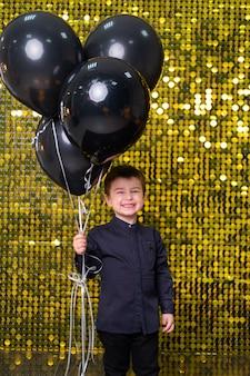 Bambino che tiene in mano palloncini neri su sfondo con paillettes di paillettes dorate lucide