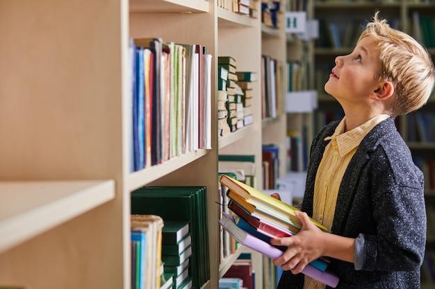 Bambino ragazzo che tiene i libri in mano in biblioteca, divertiti colto, preparandosi per la scuola