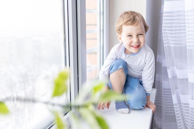 Un bambino guarda fuori dalla finestra seduto sul davanzale della finestra di casa
