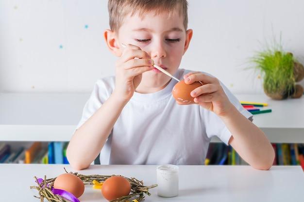 Il ragazzo del bambino dipinge le uova con vernice bianca.concetto fai da te.