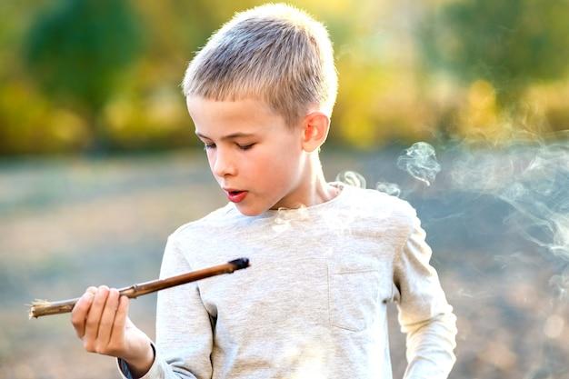 Ragazzo del bambino che gioca con il bastone di legno di fumo all'aperto.