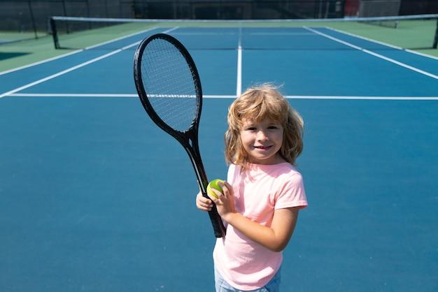 Giocatore principiante di tennis del ragazzo del bambino sul campo da tennis all'aperto.