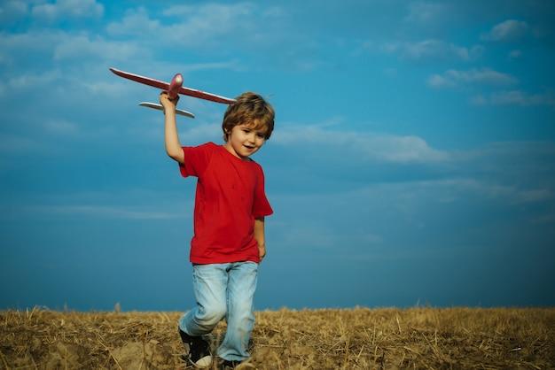 Bambino del ragazzo del bambino che gioca con l'aeroplano del giocattolo e che sogna il futuro. concetto di bambini attivi. concetto