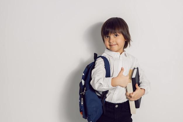 Il ragazzo del bambino con un libro di testo e uno zaino del libro sta sui pollici in su un muro bianco