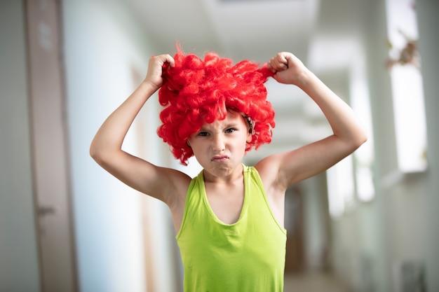 Un bambino con una parrucca brillante. ragazzo divertente con capelli artificiali rossi.
