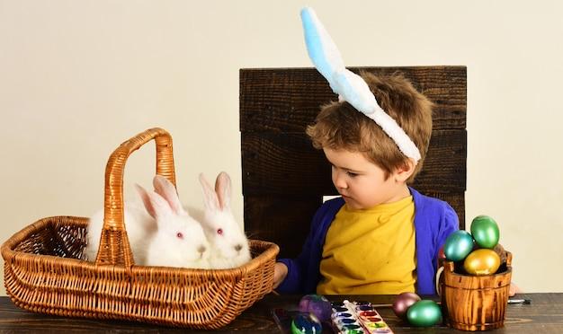 Bambino in orecchie da coniglio il giorno di pasqua. ragazzino con cesto con uova dipinte e conigli in cesto.