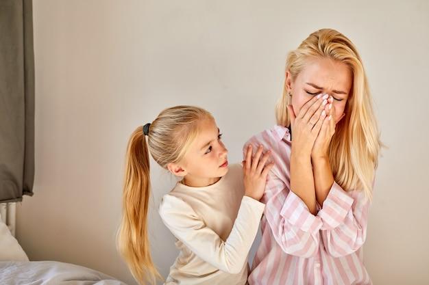 Il bambino calma la madre che piange, cerca di aiutare, chiede cosa è successo, si siedono sul letto a casa