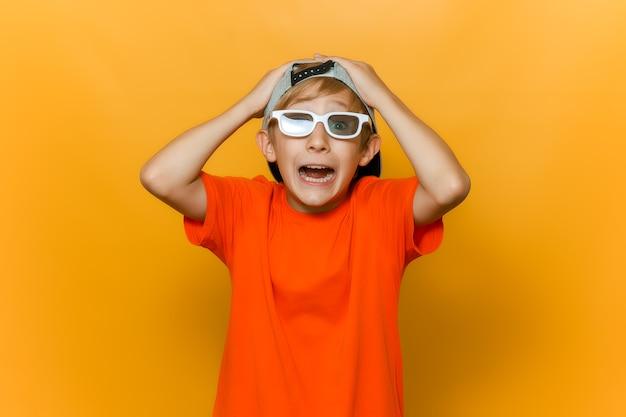 Un bambino con berretto e occhiali per guardare film gli ha afferrato la testa con entrambe le mani e mostra emozioni di paura