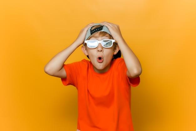 Un bambino con un berretto e occhiali per guardare film gli ha afferrato la testa con entrambe le mani e ha attorcigliato le labbra in un tubo e mostra emozioni di sorpresa