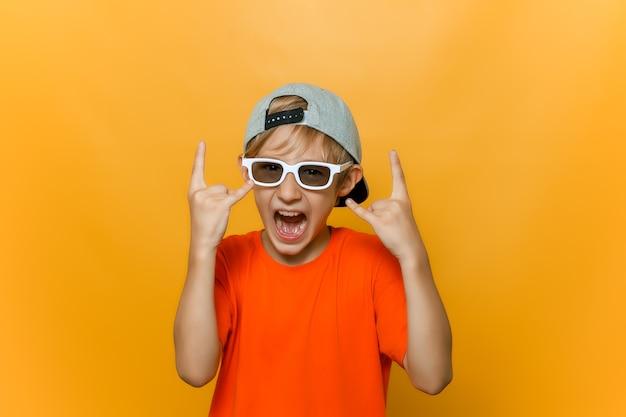 Un bambino con un berretto e occhiali per guardare film mostra gesti di metalli pesanti e grida ad alta voce