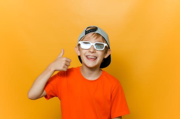 Un bambino con berretto e occhiali per guardare film mostra un pollice in alto e ride allegramente