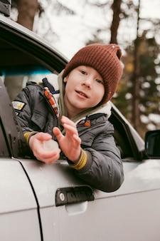 Bambino in macchina in posa durante un viaggio su strada