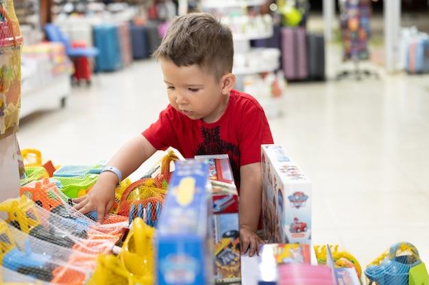 Il bambino sceglie un giocattolo nel negozio.