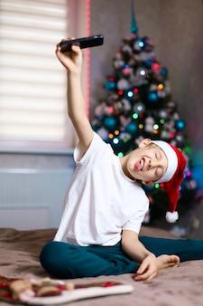 Un bambino con un cappello di natale di babbo natale è felice sullo sfondo dell'albero di natale