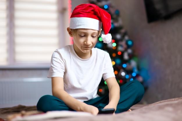 Un bambino in un cappello di babbo natale sullo sfondo di una ghirlanda