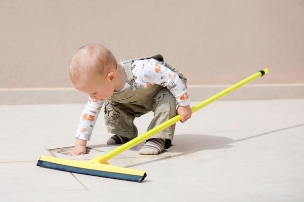 Bambino che pulisce un pavimento. il ragazzino sveglio del bambino fa la pulizia della casa. il ragazzo pulisce il pavimento.