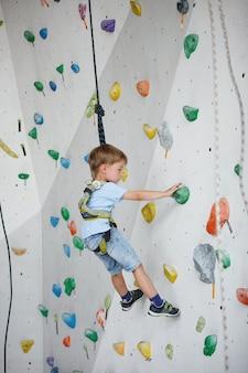 Bambino che si arrampica su un alto muro