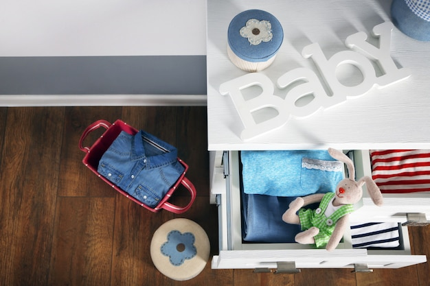 Vestiti del bambino in cassettiera in legno, primi piani