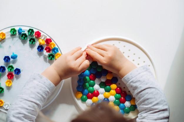 Il bambino raccoglie mosaico colorato nella vista dall'alto dell'asilo.