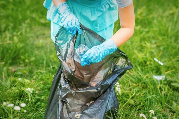 Il bambino raccoglie la spazzatura di plastica dall'erba gettando immondizia nel sacco della spazzatura nel parco