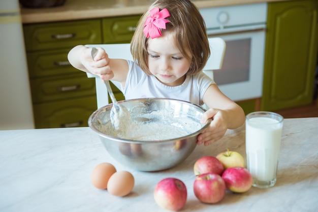 Un bambino cucina in cucina. il concetto di educazione, famiglia, cucina