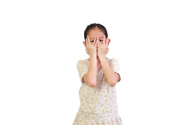 Bambino che copre gli occhi mentre si guarda attraverso lo spazio tra le dita su bianco