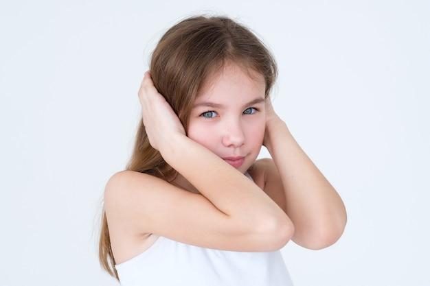Bambino che copre le orecchie con la mano sul muro bianco.