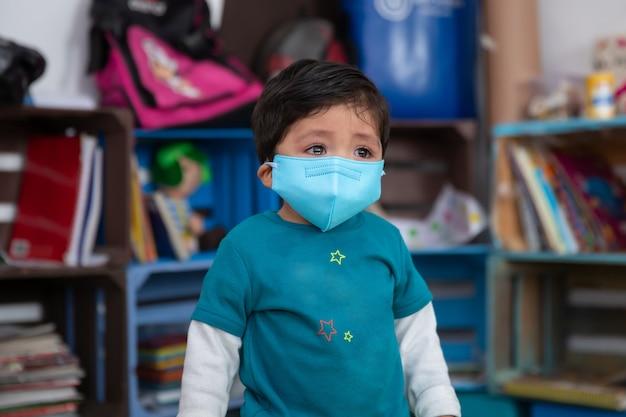 Bambino che piange tornando a scuola indossando la maschera facciale