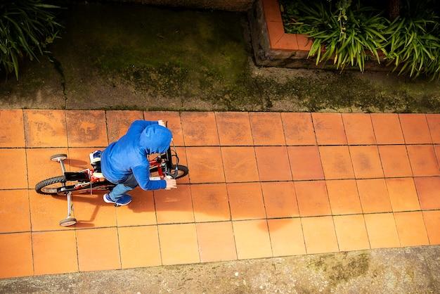 Bambino in bicicletta sulla vista dall'alto della strada sulla strada rossa