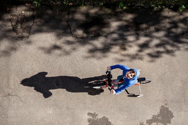 Il bambino che va in bicicletta sulla scena urbana di vista superiore della strada gode e sorride